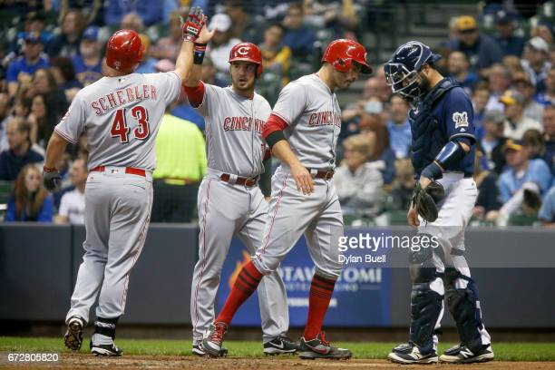 Scott Schebler Eugenio Suarez and Joey Votto of the Cincinnati Reds celebrate after Schebler hit a home run in the third inning against the Milwaukee...