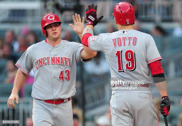 Scott Schebler of the Cincinnati Reds is congratulated by Joey Votto after scoring a third inning run against the Atlanta Braves at SunTrust Park on...