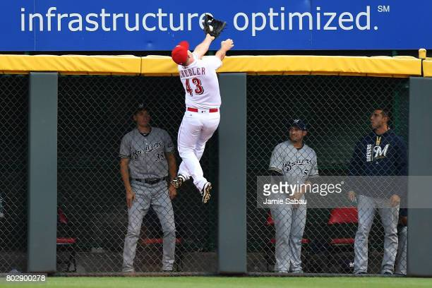 Scott Schebler of the Cincinnati Reds leaps to make a catch and rob Stephen Vogt of the Milwaukee Brewers of a home run in the second inning at Great...