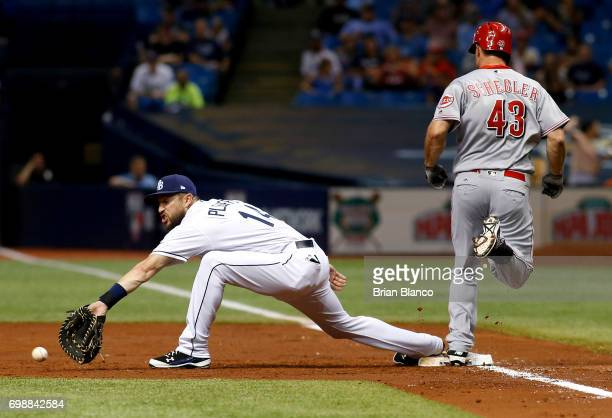 Scott Schebler of the Cincinnati Reds reaches first base on an infield single ahead of first baseman Trevor Plouffe of the Tampa Bay Rays during the...
