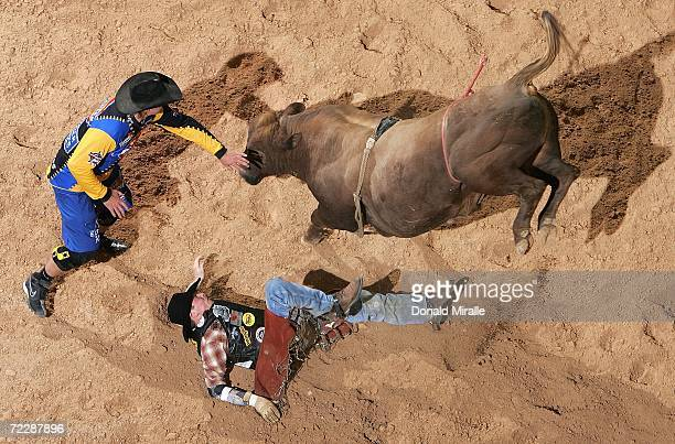 Scott Schiffner of the US tries to get away from ''Too Sharp'' as a Bullfighter comes in to help during the Professional Bull Riders World Finals on...