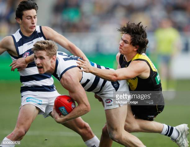 Scott Selwood of the Cats gets tackled by Daniel Rioli of the Tigers during the round 21 AFL match between the Geelong Cats and the Richmond Tigers...