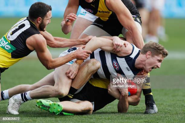 Scott Selwood of the Cats gets tackled by Shane Edwards of the Tigers during the round 21 AFL match between the Geelong Cats and the Richmond Tigers...
