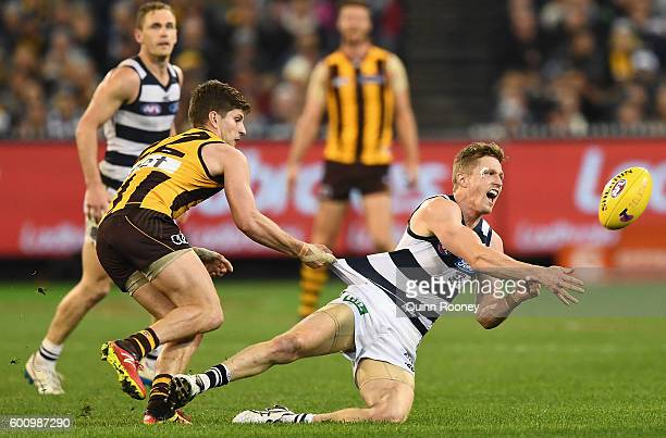 Scott Selwood of the Cats handballs whilst being tackled Luke Breust of the Hawks during the 2nd AFL Qualifying Final match between the Geelong Cats...