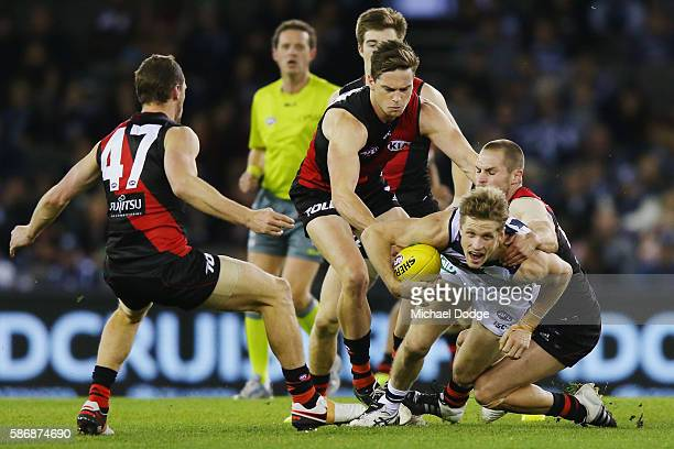Scott Selwood of the Cats is tackled by David Zaharakis of the Bombers during the round 20 AFL match between the Geelong Cats and the Essendon...
