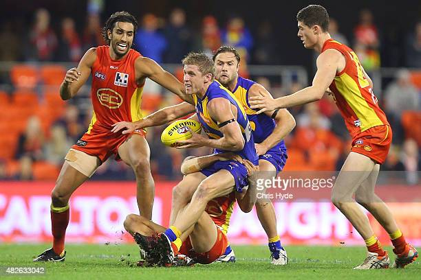 Scott Selwood of the Eagles is tackled during the round 18 AFL match between the Gold Coast Suns and the West Coast Eagles at Metricon Stadium on...