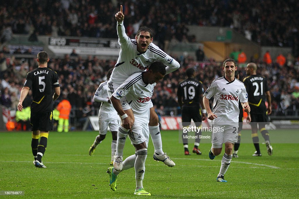 Scott Sinclair of Swansea celebrates scoring his sides second goal as Danny Graham jumps on his back during the Barclays Premier League match between...