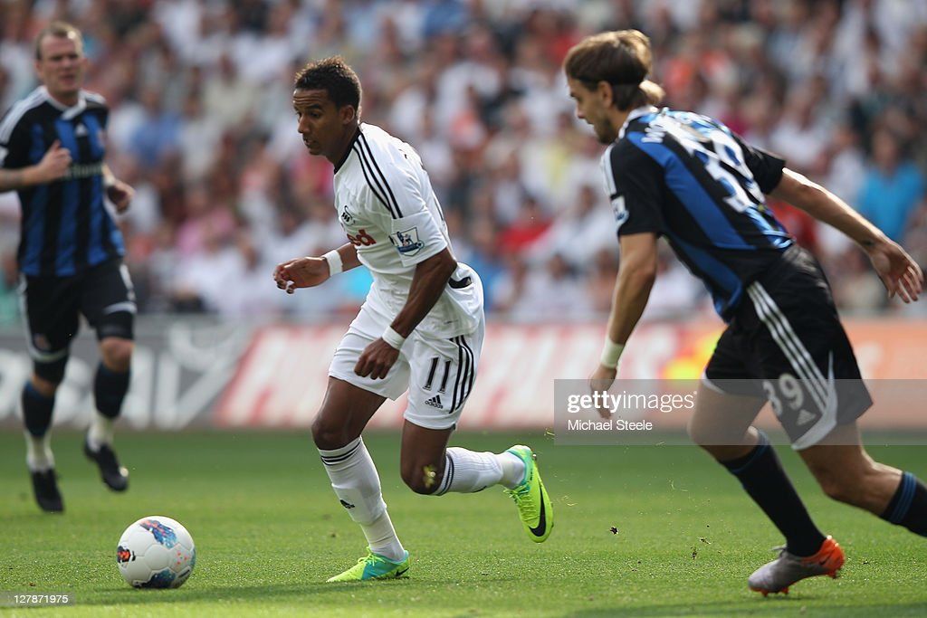 Scott Sinclair (C) of Swansea City takes on Jonathan Woodgate (R) of Stoke City during the Barclays Premier League match between Swansea City and Stoke City at the Liberty Stadium on October 2, 2011 in Swansea, Wales.