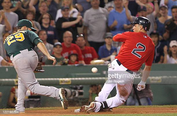 Scott Sizemore of the Oakland Athletics fields a late throw as Jacoby Ellsbury of the Boston Red Sox slides into third at Fenway Park August 26 2011...