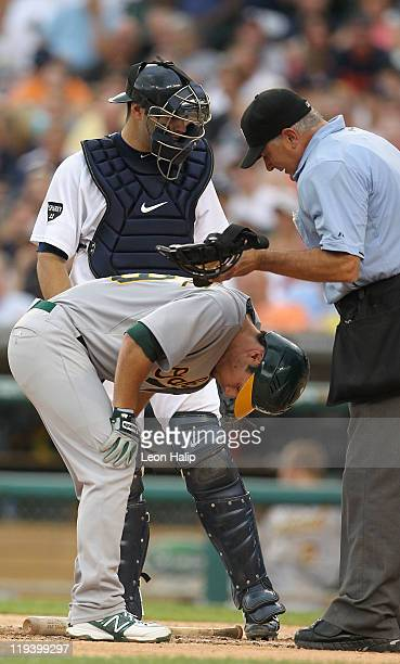 Scott Sizemore of the Oakland Athletics kneels down after getting hit in the left jaw by a pitch from Rich Porcello of the Detroit Tigers in the...