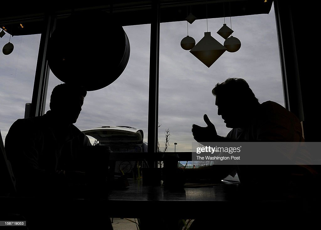 Scott Soucy chats about the national debt with (L) Wyatt Freed, a local pilot at a Starbucks coffee shop in Middletown, DE. Soucy often engages people as they pass by or are sitting near him. His usual opening line is, 'Hi there, do you want to talk about the national debt?' Scott Soucy is a man on a mission. He wants the world to know that he thinks that the U.S. debt can be paid-down if everyone just chipped in a little. The limo driver takes every chance he gets to offer up his message. (Photo by Michael S. Williamson/The Washington Post via Getty Images
