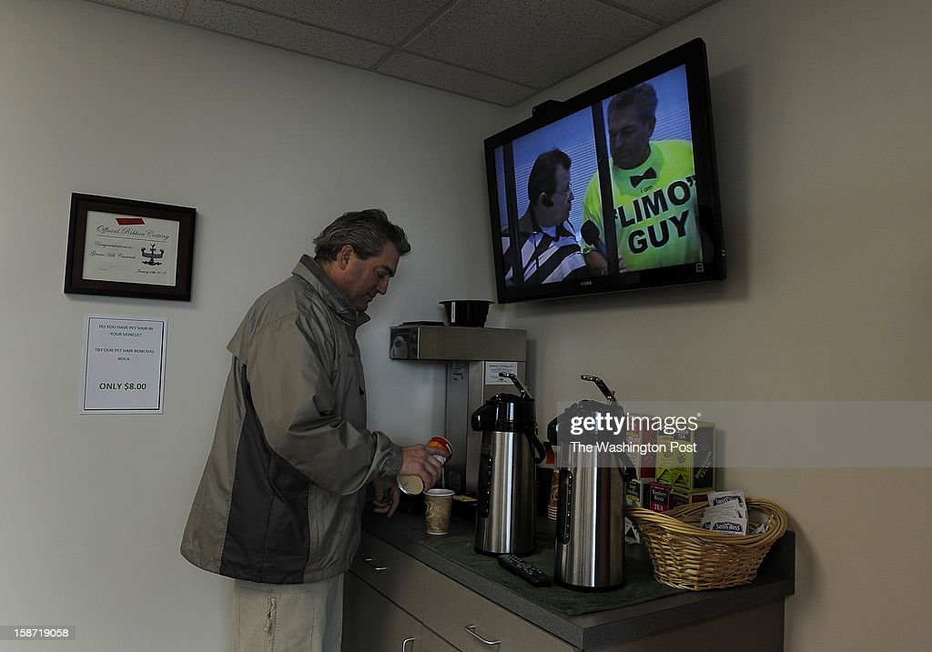 Scott Soucy gets some coffee at a car wash. Coincidentally, his local TV show was on the air when he stopped by (that's Soucy in the 'Limo Guy' shirt on the screen). Scott Soucy is a man on a mission. He wants the world to know that he thinks that the U.S. debt can be paid-down if everyone just chipped in a little. The limo driver takes every chance he gets to offer up his message. (Photo by Michael S. Williamson/The Washington Post via Getty Images