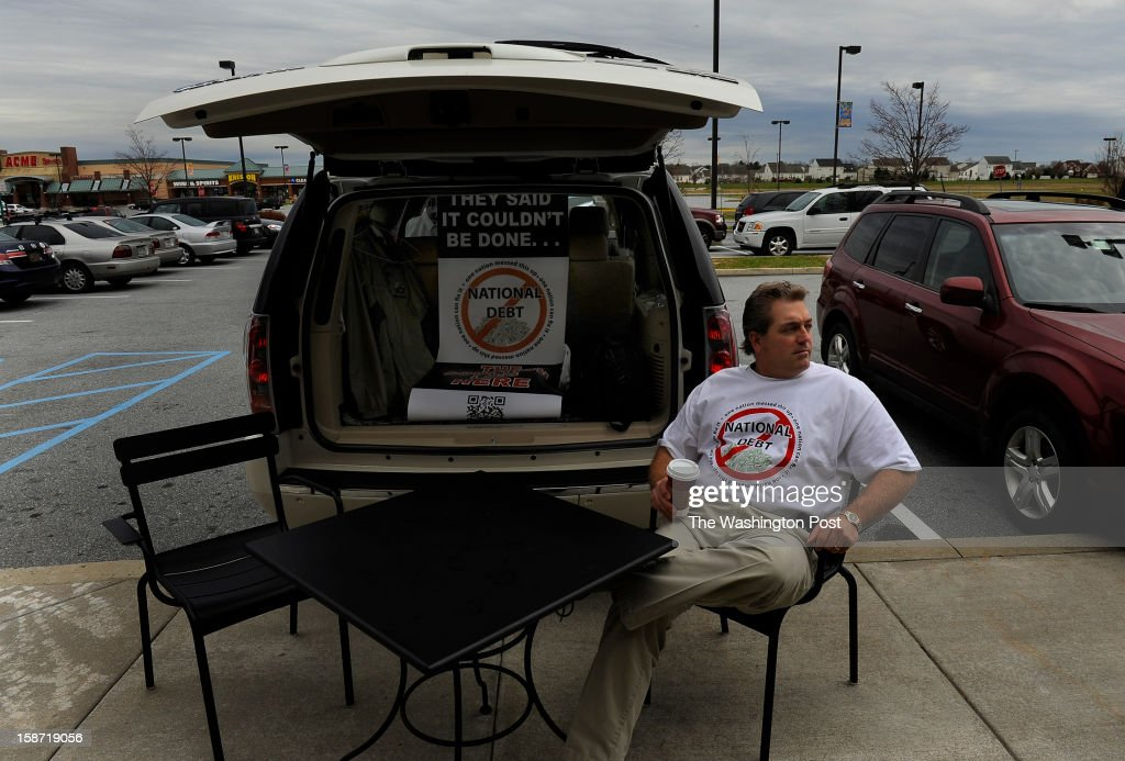 Scott Soucy sits in front of a Starbucks coffee shop in Middletown, DE waiting to engage people as they pass by. His usual opening line is, 'Hi there, do you want to talk about the national debt?' Scott Soucy is a man on a mission. He wants the world to know that he thinks that the U.S. debt can be paid-down if everyone just chipped in a little. The limo driver takes every chance he gets to offer up his message. (Photo by Michael S. Williamson/The Washington Post via Getty Images