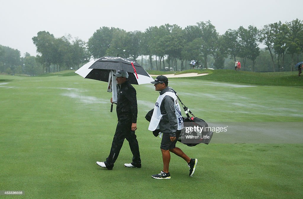 Scott Stallings of the United States and his caddie Jon Yarborough walk across the tenth fairway during the weather-delayed second round of the 96th PGA Championship at Valhalla Golf Club on August 8, 2014 in Louisville, Kentucky.