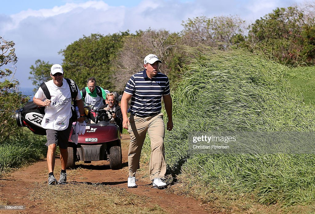 Scott Stallings (R) walks back to the clubhouse after play was suspended due to high winds during the replay of the first round of the Hyundai Tournament of Champions at the Plantation Course on January 6, 2013 in Kapalua, Hawaii.