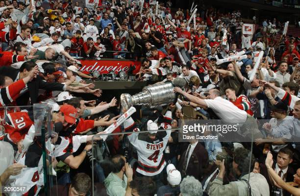 Scott Stevens of the New Jersey Devils carries the Stanley Cup holds up the Stanley Cup after beating the Mighty Ducks of Anaheim in game seven of...