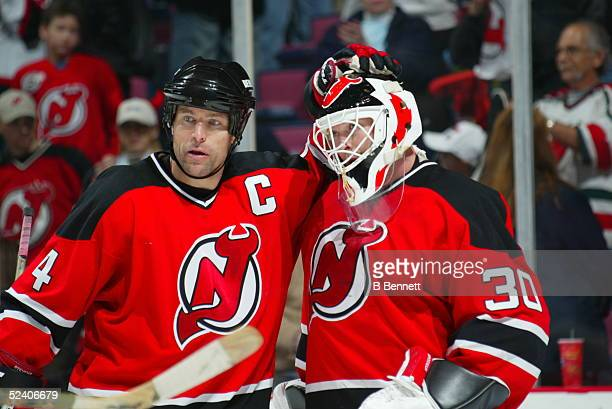 Scott Stevens of the New Jersey Devils celebrates with teammate Martin Brodeur after their NHL game circa 2004 at Continental Airlines Arena in East...