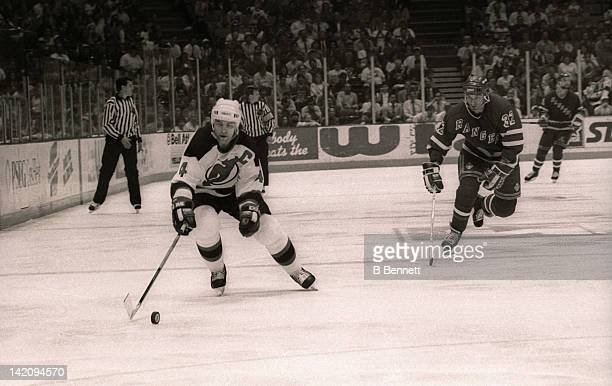 Scott Stevens of the New Jersey Devils skates down the puck as Stephane Matteau of the New York Rangers follows behind during Game 6 of the Eastern...