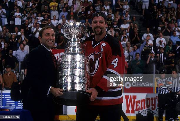 Scott Stevens of the New Jersey Devils takes the Stanley Cup from NHL commissioner Gary Bettman after the Devils defeated the Dallas Stars in Game 6...