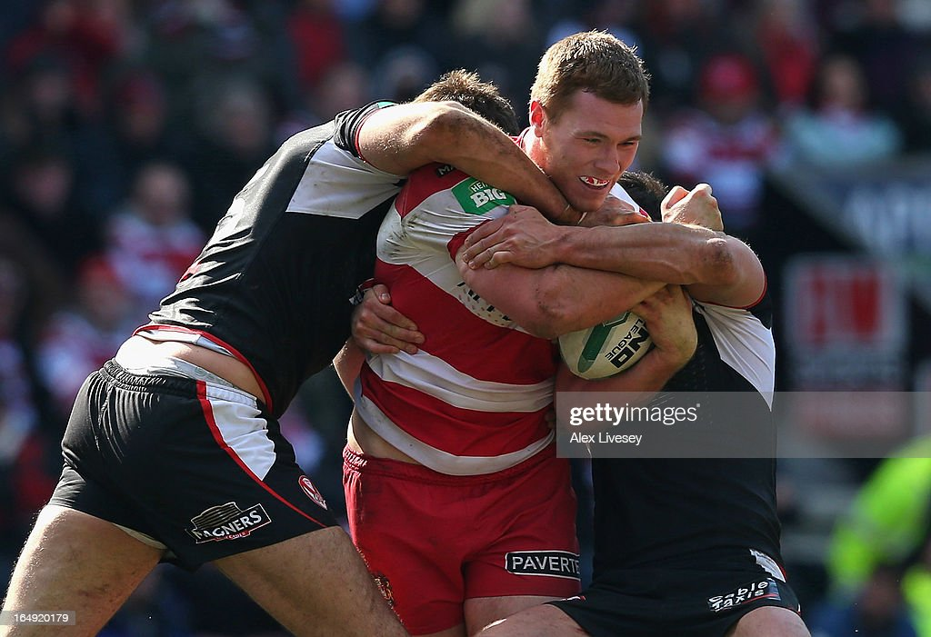 Scott Taylor of Wigan Warriors is tackled by Alex Walmsley of St Helens during the Super League match between Wigan Warriors and St Helens at DW Stadium on March 29, 2013 in Wigan, England.