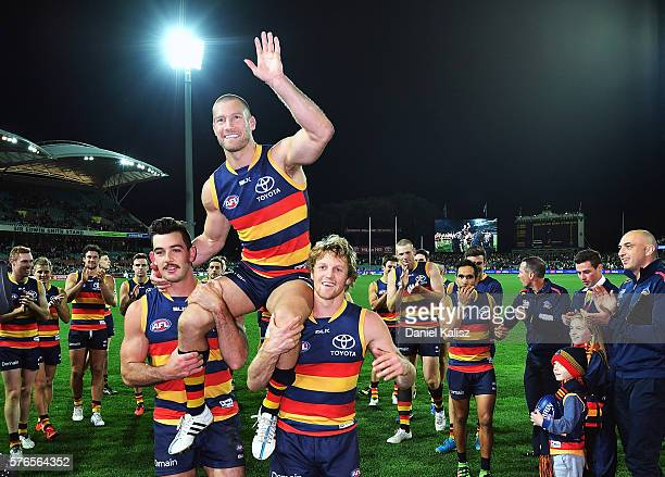 Scott Thompson of the Crows is chaired off the field after playing his 300th game by Taylor Walker and Rory Sloane of the Crows during the round 17...