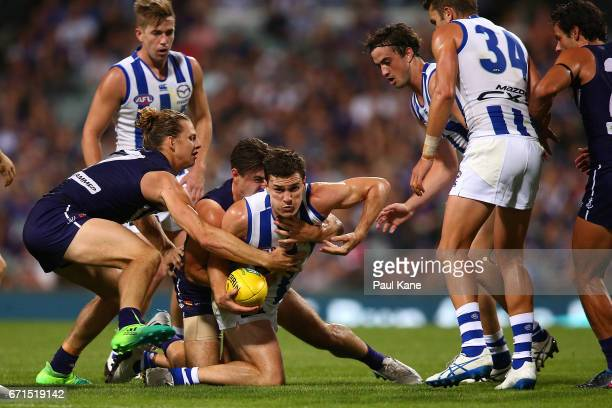 Scott Thompson of the Kangaroos gets tackled by Shane Kersten and Nathan Fyfe of the Dockers during the round five AFL match between the Fremantle...