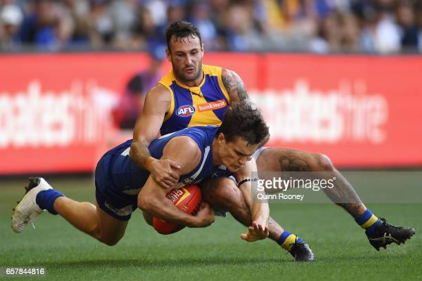 Scott Thompson of the Kangaroos is tackled by Chris Masten of the Eagles during the round one AFL match between the North Melbourne Kangaroos and the...