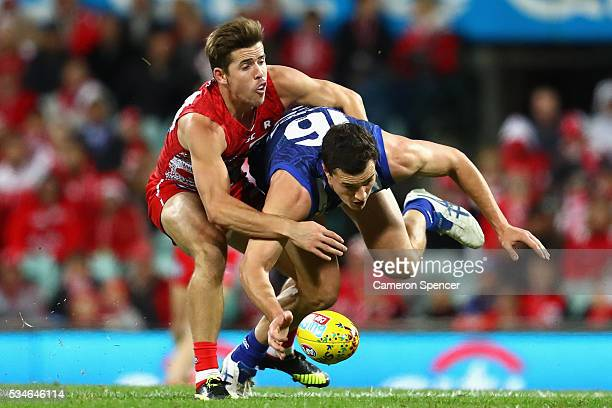 Scott Thompson of the Kangaroos is tackled by Jake Lloyd of the Swans during the round 10 AFL match between the Sydney Swans and the North Melbourne...
