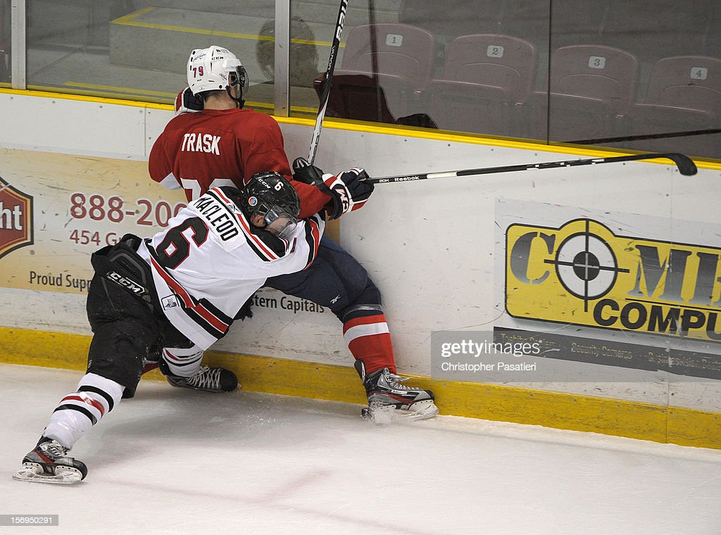 Scott Trask #79 of the Summerside Western Capitals is checked by Daniel MacLeod #6 of the Weeks Crushers during the game on November 25, 2012 at the Consolidated Credit Union Place in Summerside, Prince Edward Island, Canada.