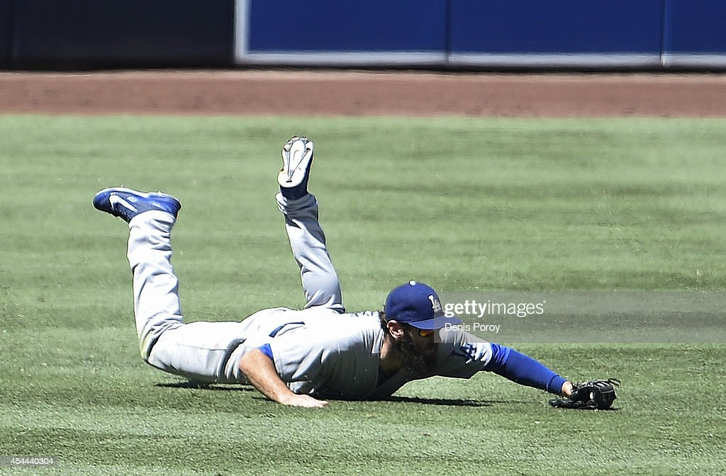 Scott Van Slyke #33 of the Los Angeles Dodgers makes a diving catch on a ball hit by Jedd Gyorko #9 of the San Diego Padres during the fourth inning of a baseball game at Petco Park August, 31, 2014 in San Diego, California.