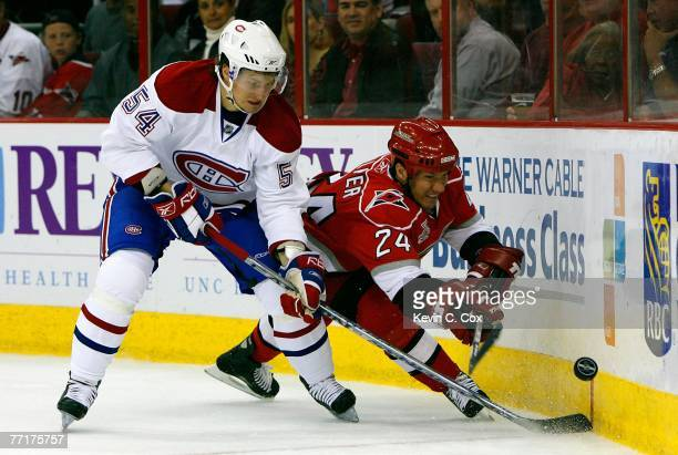 Scott Walker of the Carolina Hurricanes battles for a loose puck against Mikhail Grabovski of the Montreal Canadiens during first period October 3...