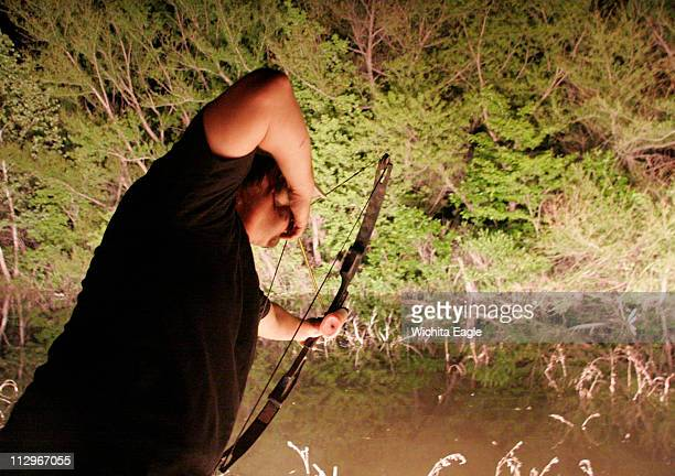 Scott Whitehead takes a shot on a carp in the nighttime shallows of El Dorado Reservoir in Kansas He likes the peacefulness of night bowfishing plus...