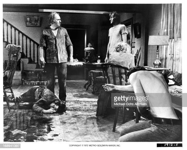 Scott Wilson lies dead as Rod Steiger stands over him with Timothy Scott Katherine Squire and Ed Lauter in a scene from the film 'LollyMadonna XXX'...