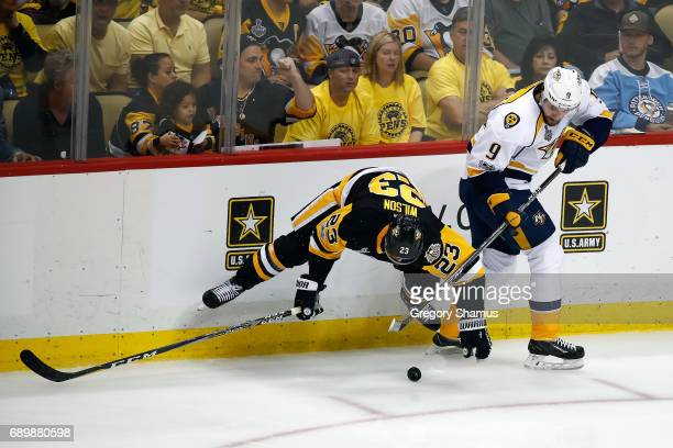 Scott Wilson of the Pittsburgh Penguins and Filip Forsberg of the Nashville Predators get tied up along the boards in Game One of the 2017 NHL...
