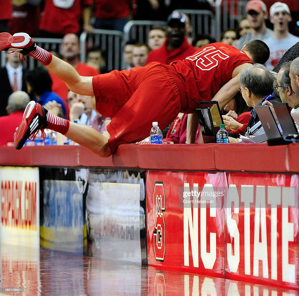 Scott Wood #15 of the North Carolina State Wolfpack dives onto press row to save a loose ball against the North Carolina Tar Heels during play at PNC Arena on January 26, 2013 in Raleigh, North Carolina.