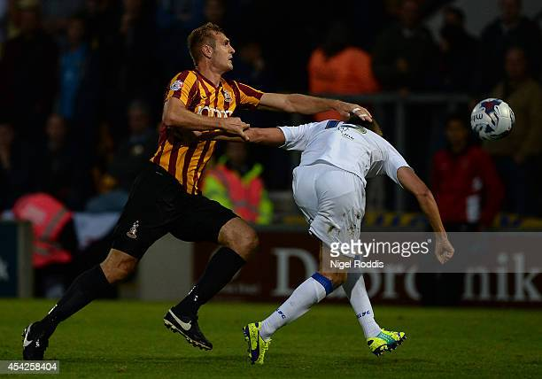 Scott Wootton of Leeds United challenged by James Hanson of Bradford City during the Capital One Cup second round match between Bradford City and...
