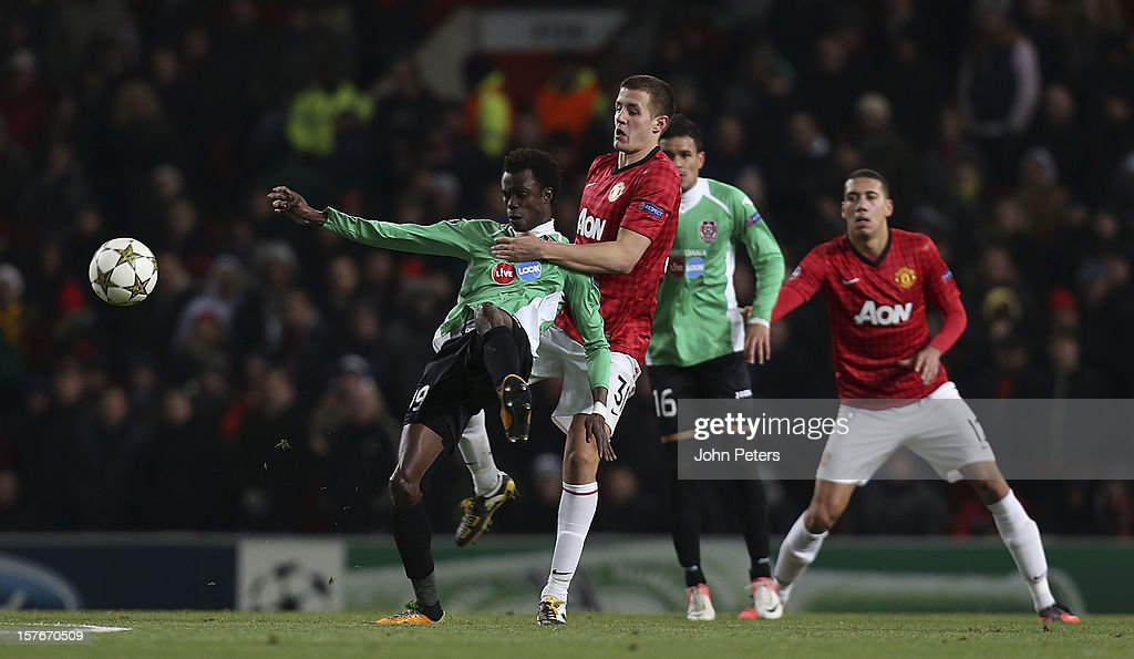 Scott Wootton of Manchester United in action with Modou Sougou of CFR 1907 Cluj during the UEFA Champions League Group H match between Manchester United and CFR 1907 Cluj at Old Trafford on December 5, 2012 in Manchester, England.
