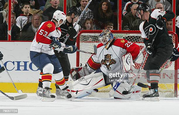 Scottie Upshall and Jeff Carter of the Philadelphia Flyers take a shot on goal against Brett McLean and Tomas Vokoun of the Florida Panthers on...