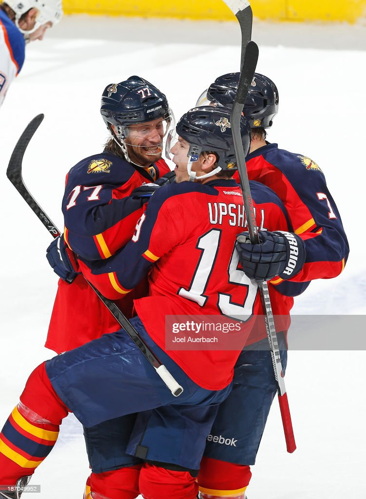 <a gi-track='captionPersonalityLinkClicked' href=/galleries/search?phrase=Scottie+Upshall&family=editorial&specificpeople=209198 ng-click='$event.stopPropagation()'>Scottie Upshall</a> #19 is congratulated by <a gi-track='captionPersonalityLinkClicked' href=/galleries/search?phrase=Tom+Gilbert&family=editorial&specificpeople=687083 ng-click='$event.stopPropagation()'>Tom Gilbert</a> #77 and Dmitry Kulikov #7 of the Florida Panthers that tied the game against the Edmonton Oilers in the third period at the BB&T Center on November 5, 2013 in Sunrise, Florida. The Oilers defeated the Panthers 4-3 in overtime.