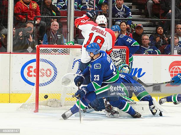 Scottie Upshall of the Florida Panthers and Alexander Edler of the Vancouver Canucks watch the puck enter the goal behind Roberto Luongo of the...
