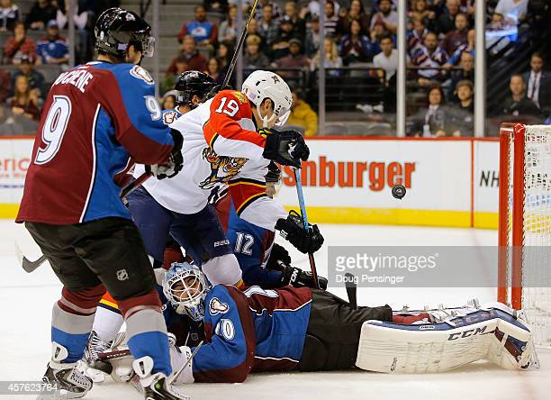 Scottie Upshall of the Florida Panthers is unable to control the puck as goalie Reto Berra of the Colorado Avalanche hits the ice at Pepsi Center on...