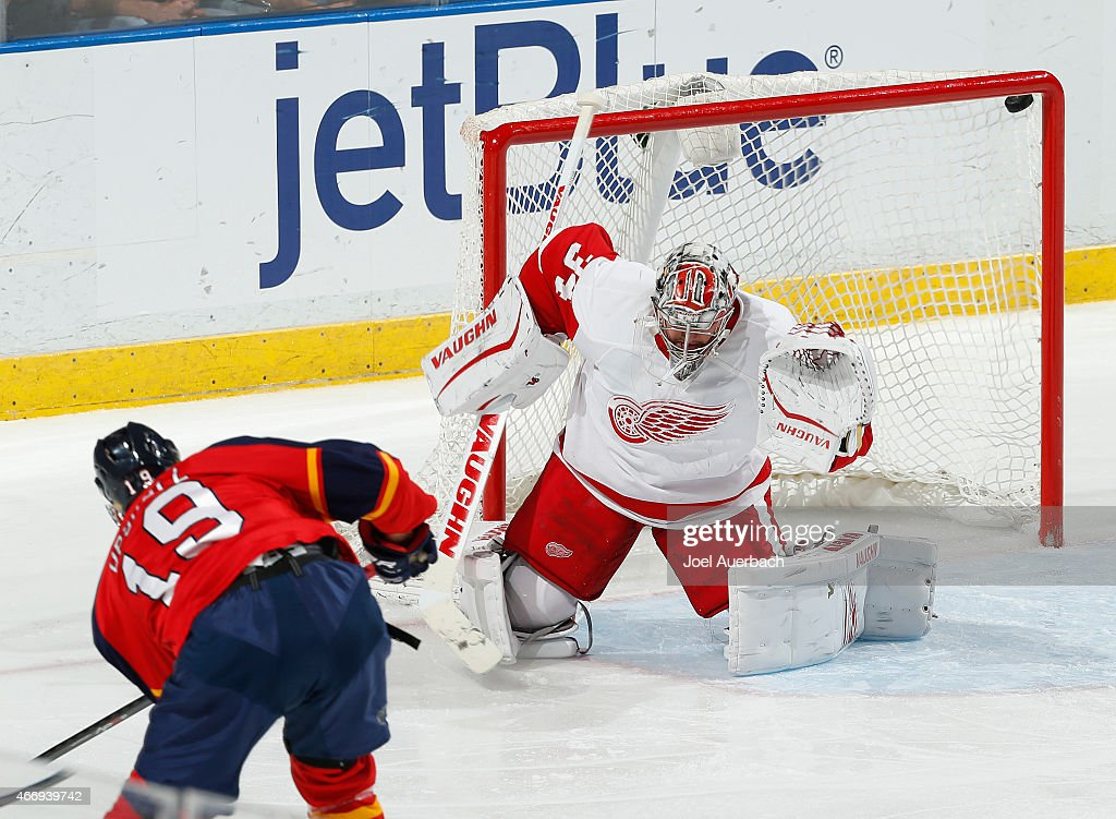 <a gi-track='captionPersonalityLinkClicked' href=/galleries/search?phrase=Scottie+Upshall&family=editorial&specificpeople=209198 ng-click='$event.stopPropagation()'>Scottie Upshall</a> #19 of the Florida Panthers shoots the puck under the crossbar past Goaltender <a gi-track='captionPersonalityLinkClicked' href=/galleries/search?phrase=Petr+Mrazek&family=editorial&specificpeople=6514148 ng-click='$event.stopPropagation()'>Petr Mrazek</a> #34 of the Detroit Red Wings for a third period goal at the BB&T Center on March 19, 2015 in Sunrise, Florida. The Panthers defeated the Red Wings 3-1.