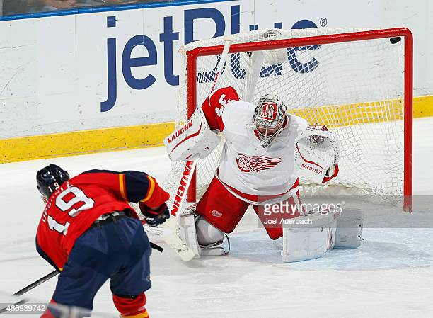 Scottie Upshall of the Florida Panthers shoots the puck under the crossbar past Goaltender Petr Mrazek of the Detroit Red Wings for a third period...
