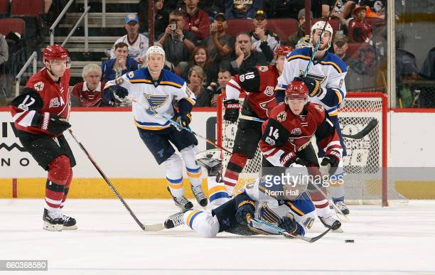 Scottie Upshall of the St Louis Blues falls to the ice in front of Clayotn Keller of the Arizona Coyotes after being tripped by Radim Vrbata of the...