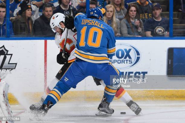 Scottie Upshall of the St Louis Blues gets checked off the puck by Matt Bartkowski of the Calgary Flames on March 25 2017 at Scottrade Center in St...