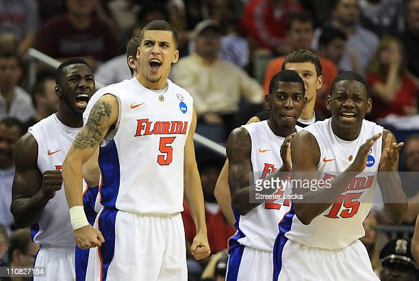 Scottie Wilbekin and Will Yeguete of the Florida Gators celebrate with the bench during their 84 to 74 win over the Brigham Young Cougars in the...