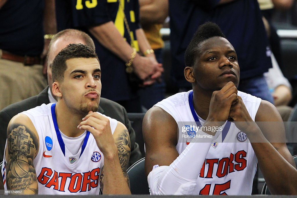 Scottie Wilbekin #5 and Will Yeguete #15 of the Florida Gators look on late in their 79 to 59 loss to the Michigan Wolverines during the South Regional Round Final of the 2013 NCAA Men's Basketball Tournament at Dallas Cowboys Stadium on March 31, 2013 in Arlington, Texas.