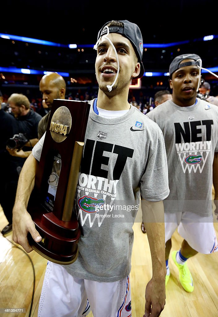 Scottie Wilbekin of the Florida Gators celebrates on the court with the trophy after defeating the Dayton Flyers 6252 in the south regional final of...