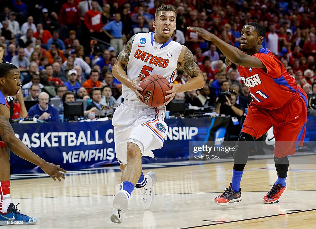 Scottie Wilbekin of the Florida Gators goes to the basket as Scoochie Smith of the Dayton Flyers defends during the south regional final of the 2014...