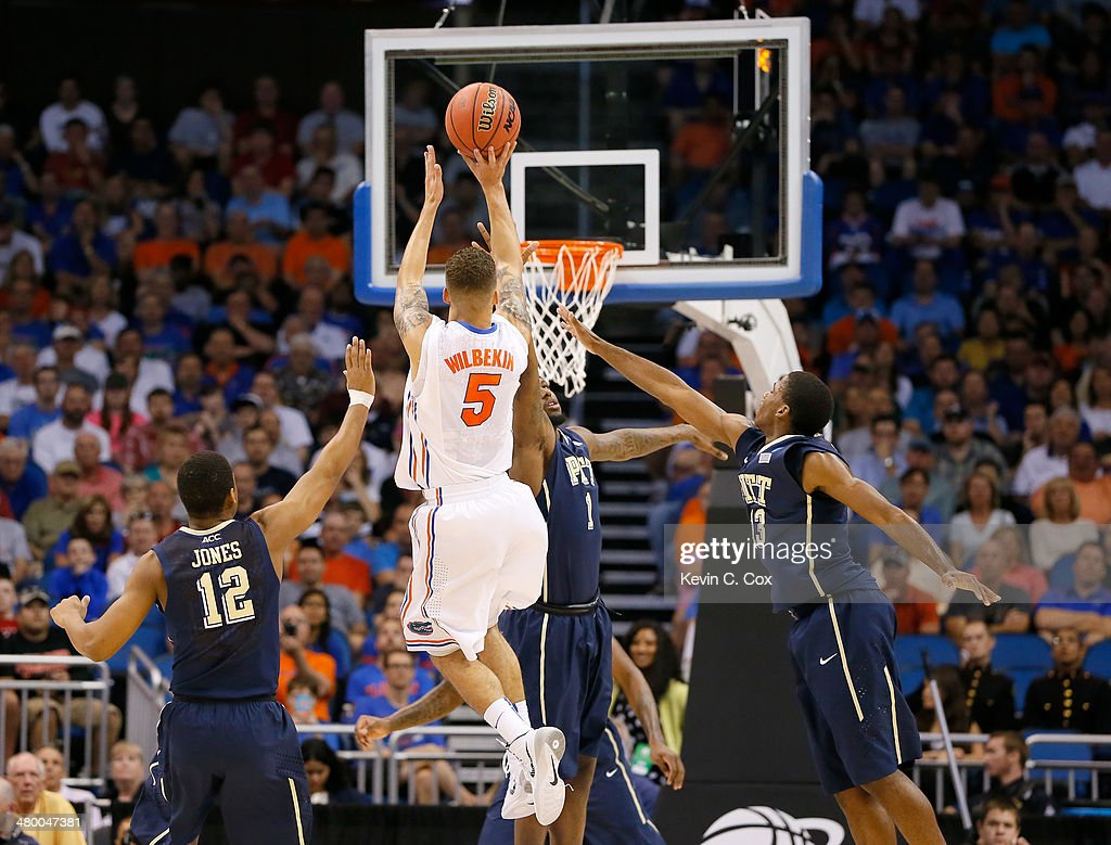 Scottie Wilbekin of the Florida Gators makes a threepointer as time expires in the first half over Jamel Artis of the Pittsburgh Panthers during the...